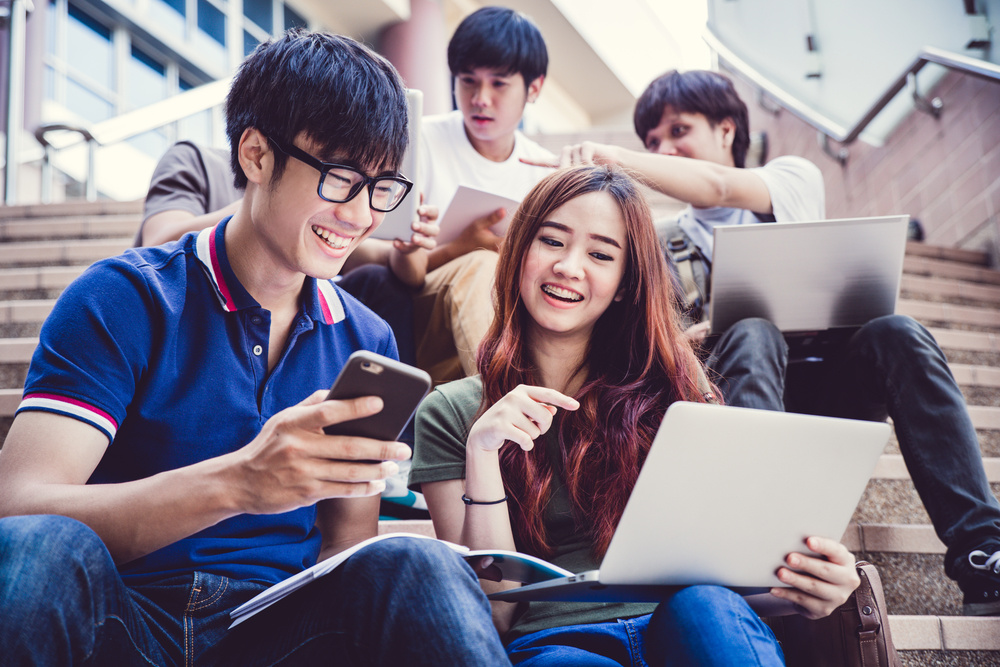 asian-students-discussing-something-holding-smartphone-laptop