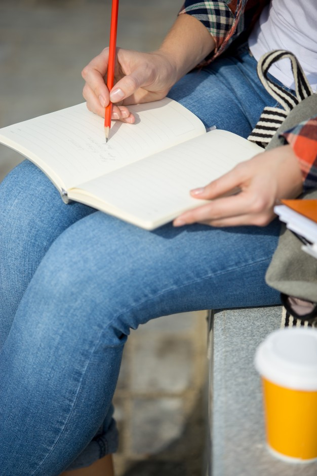 student-lady-writing-open-notebook-with-pencil_1163-2546